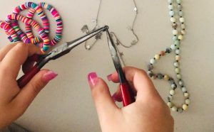 Handoush crafts necklaces, keychains, bracelets, and more for her business.