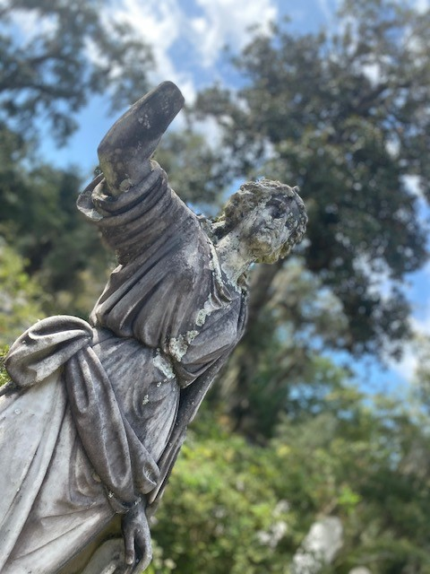 I watch a long-worn statue with a broken off hand, still peering over the deat at a Savannah cemetery.